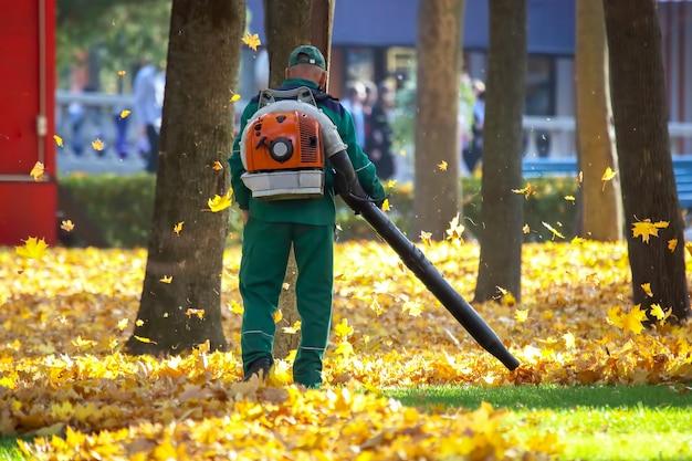 공원에서 일하는 것은 송풍기로 단풍을 제거합니다.