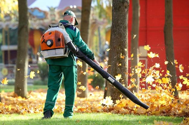 Работа в парке убирает листья с помощью воздуходувки