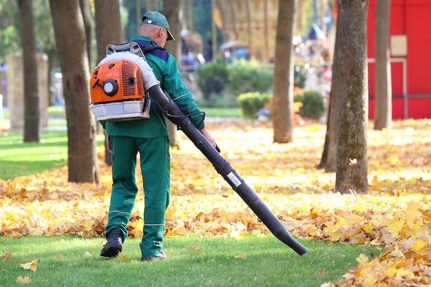 공원에서 일하는 것은 송풍기로 잎을 제거합니다