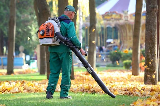 Работая в парке, убирают листья с помощью воздуходувки
