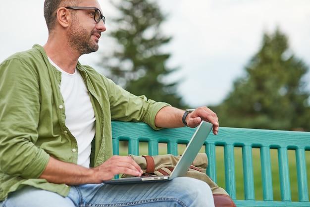 야외 벤치에 앉아 노트북을 사용하는 안경을 쓰고 공원에서 일하는 청년