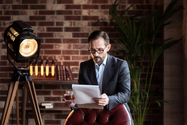 작업 문제. 열심히 일하는 자영업 잘 생긴 사업가 의자 근처에 서서 일부 문서를 검토하는 동안 위스키 한 잔을 들고