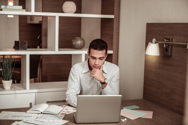 Working on laptop. smart skillful dark-haired businessman working on laptop sitting in hotel room
