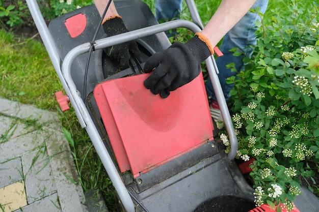 Рабочая газонокосилка на зеленой лужайке с подстриженной травой