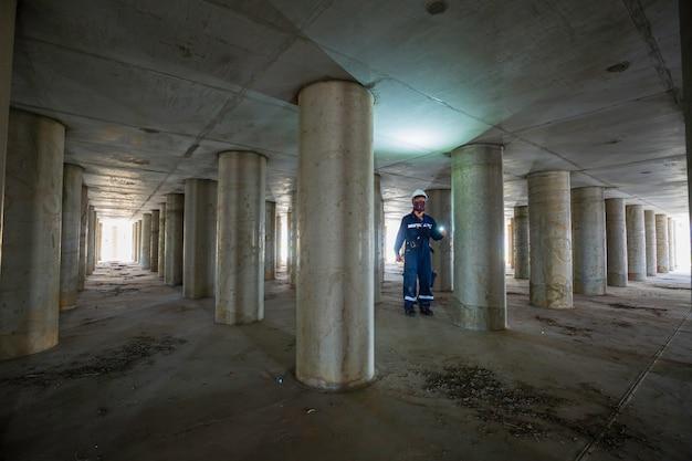 탱크 장비 터널 지하에서 작동하는 수컷 검사 기둥 탱크 아래 내부의 손전등을 사용하여.