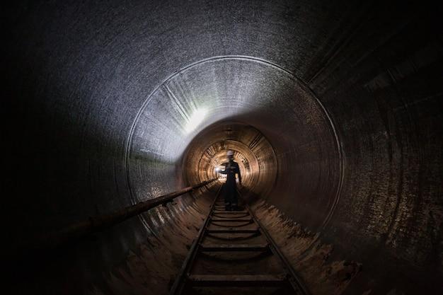 Рабочий мужской инспекционный сварной шов под землей туннеля с оборудованием с помощью фонарика.