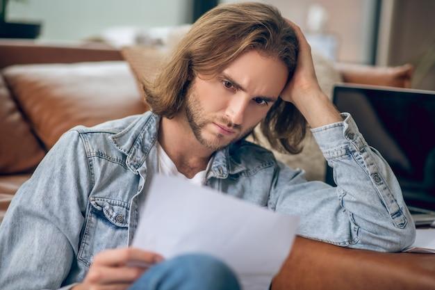 За работой. человек в джинсовой рубашке держит документы и выглядит сосредоточенным