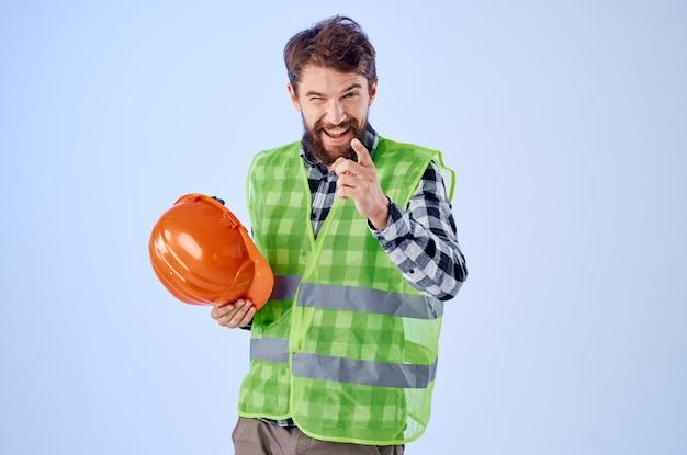 オレンジ色のヘルメット建設専門家の青い背景で働く男