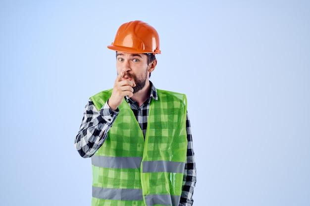 オレンジ色のヘルメット建設専門家の孤立した背景で働く男