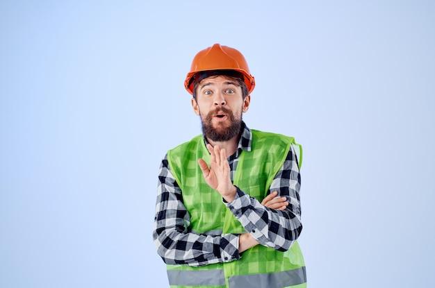 オレンジ色のヘルメット建設専門スタジオで働く男