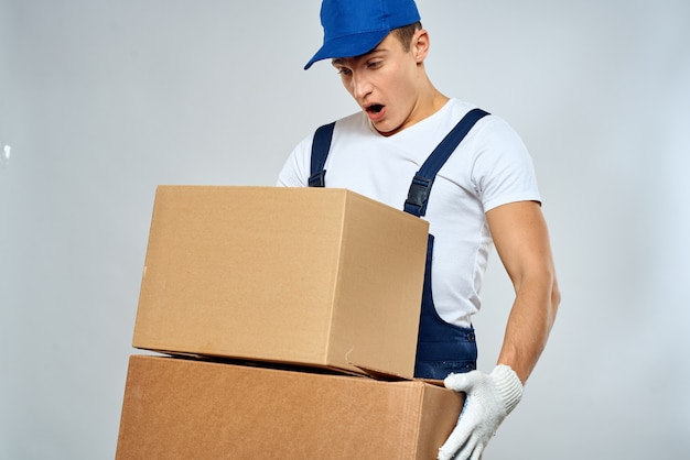 Working man in uniform with boxes in his hands delivery loader lifestyle.