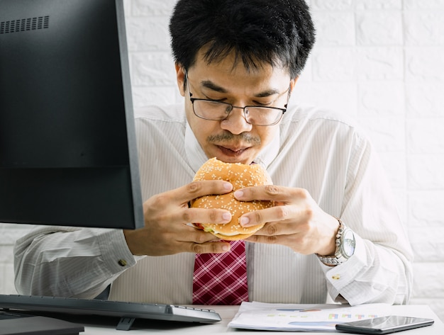Working men do not have time to urgent eating junk food hamburger while working in office