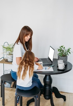 Working mom freelancer with laptop little daughter playing on table together stay at home