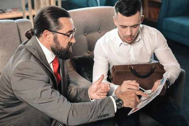 Working moments. bearded boss wearing glasses explaining working moments to his young trainee
