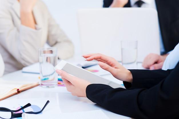 Рабочие моменты. крупный план деловых людей, работающих, сидя за столом вместе