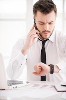 일하는 순간. 셔츠와 넥타이에 잘 생긴 젊은 수염 남자는 그의 작업 장소에서 작업