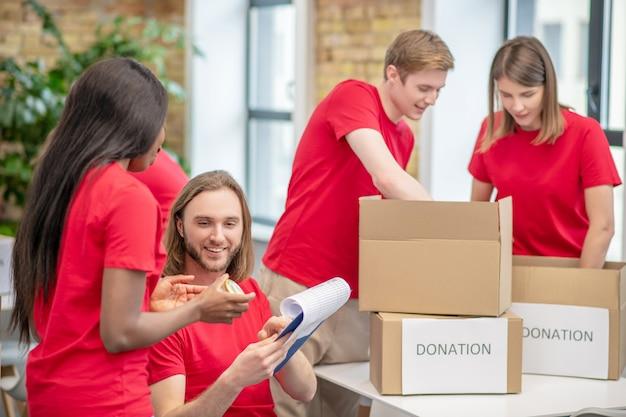 근무 분위기. 자선 센터에서 기부금을 포장하는 빨간 티셔츠에 낙관적 인 학생 자원 봉사자 의사 소통 그룹