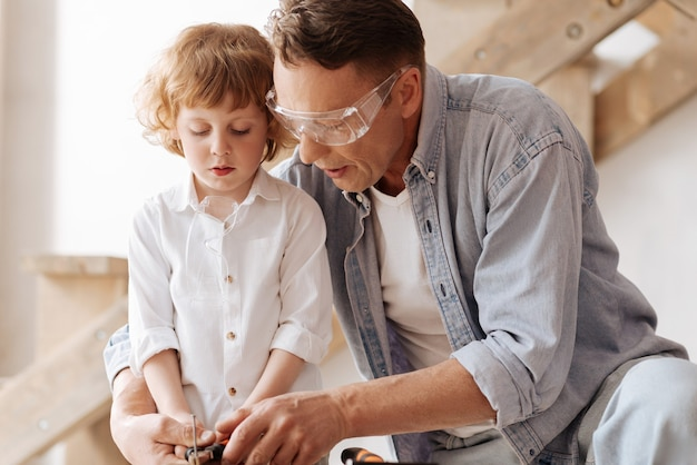 Working mood. serious father wearing protective glasses and holding pliers in both hand while embracing his son