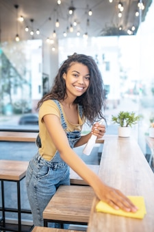 Working mood. young pretty cheerful mulatto woman with white-toothed smile wiping table in cafe in afternoon