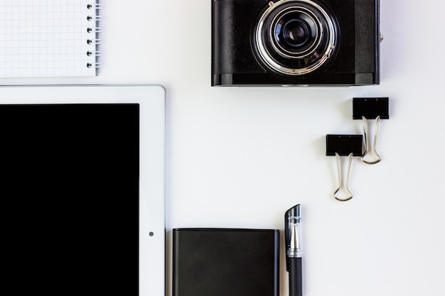 Working office space with a tablet, notepad, camera, external hard disk located on a white table,