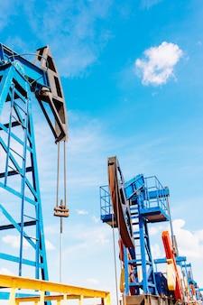 오일 필드에서 작동 오일 펌프 잭. 흰 구름과 푸른 하늘. 석유 및 석유 생산.