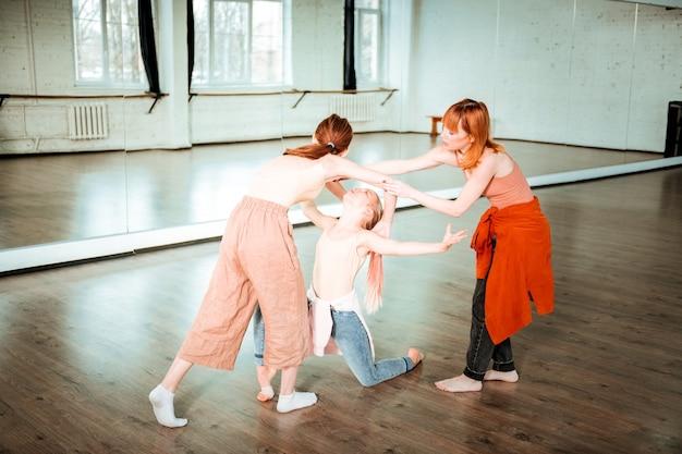 ダンスに取り組んでいます。スタジオで新しいダンスの下で働いている間忙しそうに見えるダンススクールの2人の学生 Premium写真