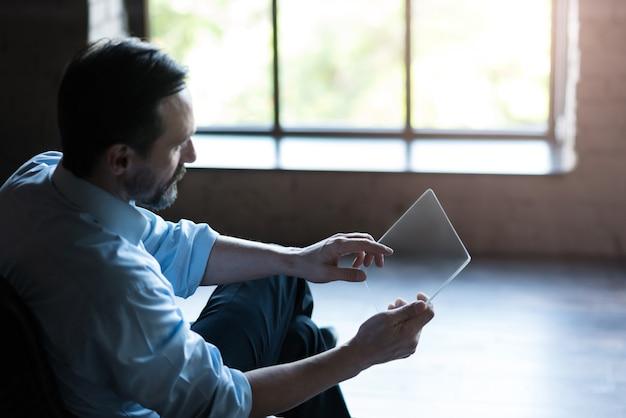 태블릿에서 작업. 태블릿을 들고 창에 앉아있는 동안 자신의 일에 집중하는 심각한 좋은 찾고 매력적인 남자