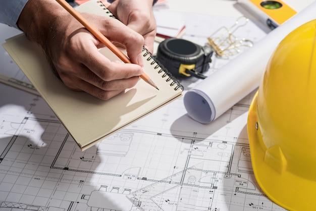 청사진 작업. 노트북에 손으로 쓰는 건설 프로젝트.