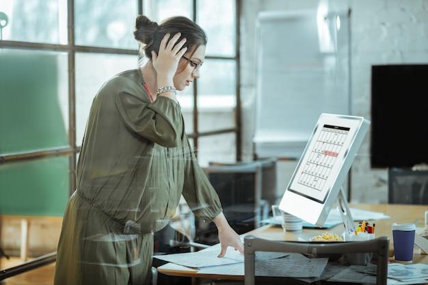 Работаю на компьютере. трудолюбивая беременная бизнесвумен в очках работает на компьютере