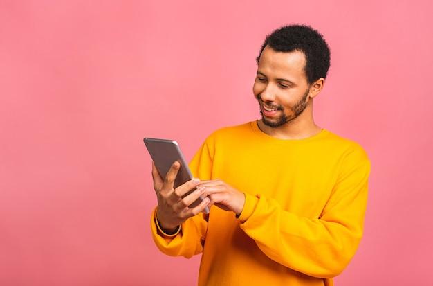 デジタルタブレットに取り組んでいます。ピンクの上に孤立して立っている間デジタルタブレットに取り組んでいる若い男の肖像画。