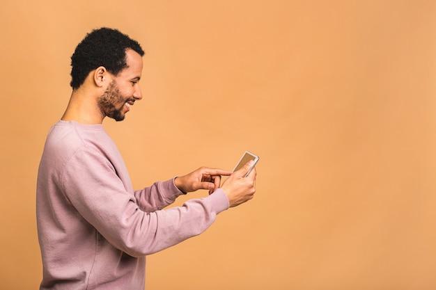デジタルタブレットに取り組んでいます。ベージュの上に孤立して立っている間デジタルタブレットに取り組んでいる若い男の背面図。