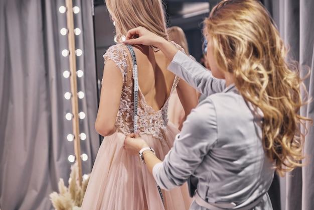 드레스 작업. 피팅 룸에 서 있는 동안 신부를 측정 하는 젊은 여자
