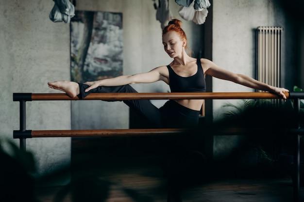Работаем над гибкостью. молодая рыжеволосая балерина подняла одну ногу на балетной планке и делает упражнения на растяжку на темном фоне студии или класса. концепция тренировки barre