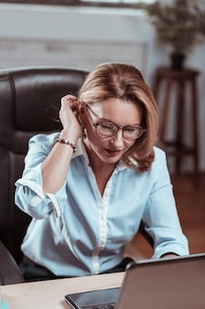 ラップトップに取り組んでいます。ラップトップで作業するオフィス服と眼鏡を着た金髪の成熟した女性