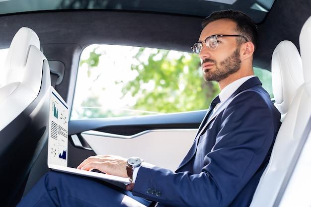 Работаю на ноутбуке. занят преуспевающий темноволосый бизнесмен, работающий на ноутбуке, сидя в машине