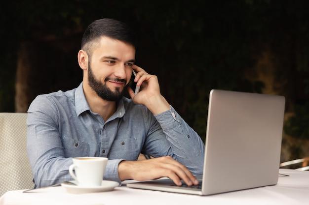 室内でラップトップに取り組んでいます。幸せな男は自宅で仕事をし、彼はテーブルでコーヒーを飲みながら座って、笑顔でスマートフォンで話します