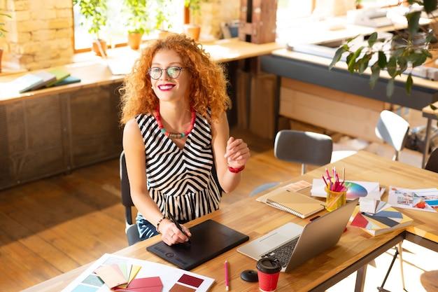 プロジェクトに取り組んでいます。新しいプロジェクトに取り組んでいる間、赤毛のデザイナーはやる気を感じます