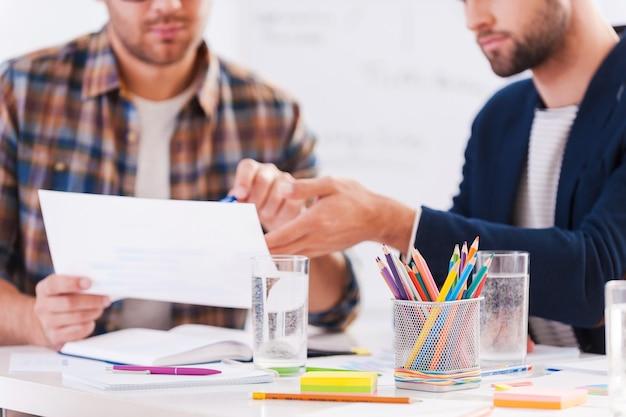 Работаем над проектом вместе. крупный план двух уверенных в себе деловых людей в элегантной повседневной одежде, сидящих вместе за столом и обсуждающих что-то
