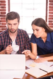 함께 프로젝트를 진행합니다. 여자가 노트북을 가리키는 동안 작업 장소에 함께 앉아 자신감이 젊은 남자와 여자