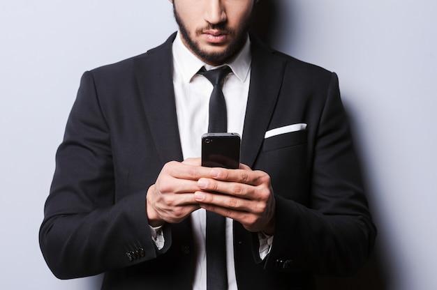 이동 중입니다. 회색 배경에 서 있는 동안 휴대 전화를 들고 formalwear에서 젊은 남자의 근접