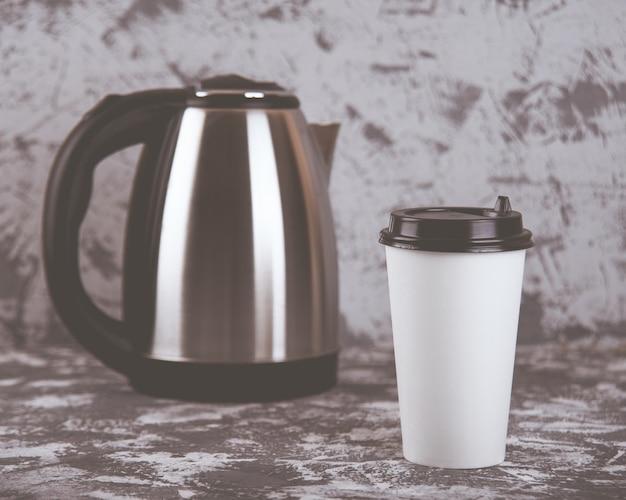 外出先での作業。灰色の石のテーブルの上のコーヒーカップと電気ケトル。スペースをコピーします。