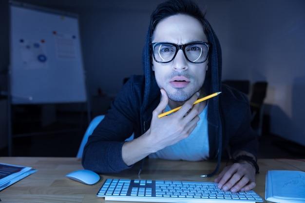 オンラインでの作業。コンピュータの画面を見ながら前かがみになり、彼のあごを保持しているハンサムな真面目な思慮深い男
