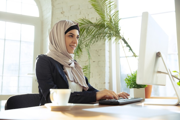 Working online. portrait of a beautiful arabian businesswoman wearing hijab while working at openspace or office. concept of occupation, freedom in business area, leadership, success, modern solution.