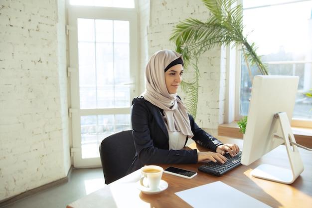 온라인 작업. 오픈스페이스나 사무실에서 일하는 동안 히잡을 쓴 아름다운 아라비아 여성 사업가의 초상화. 직업의 개념, 비즈니스 영역의 자유, 리더십, 성공, 현대적인 솔루션.