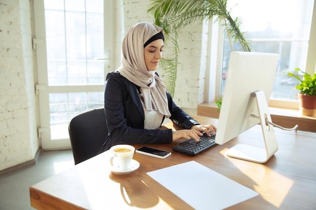 일하는 동안 히잡을 쓰고 있는 아름다운 아라비아 여성 사업가의 온라인 작업 초상화