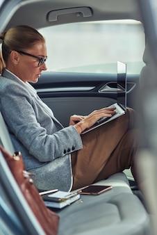 Работающий онлайн вид сбоку занятой деловой женщины средних лет, использующей ноутбук, сидя на спине