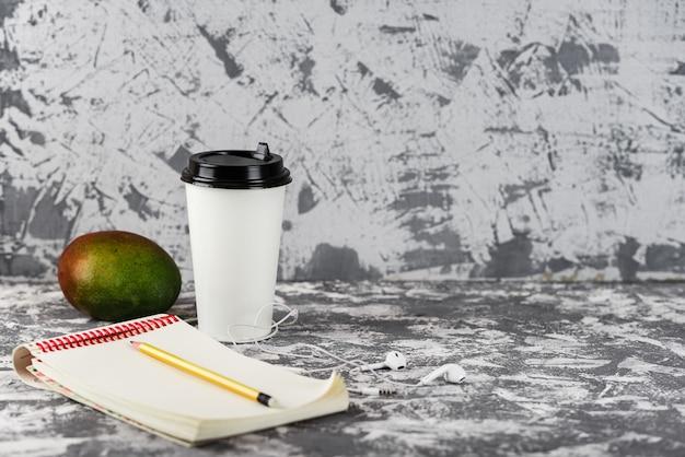 外出先での仕事や教育。コーヒーカップ、マンゴーフルーツ、電話、灰色の石のテーブルにメモ帳のスタック。スペースをコピーします。