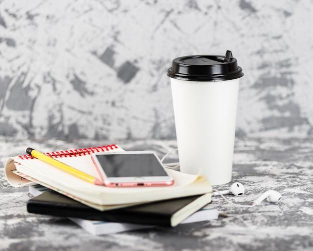 外出先での仕事や教育。コーヒーカップ、マンゴーフルーツ、ピンクのスマートフォン、灰色の石のテーブルにメモ帳のスタック。スペースをコピーします。