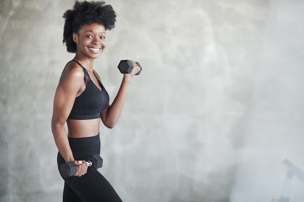 Working out against wall. studio shot of young woman that stands in front of grey background with dumbbells in hands
