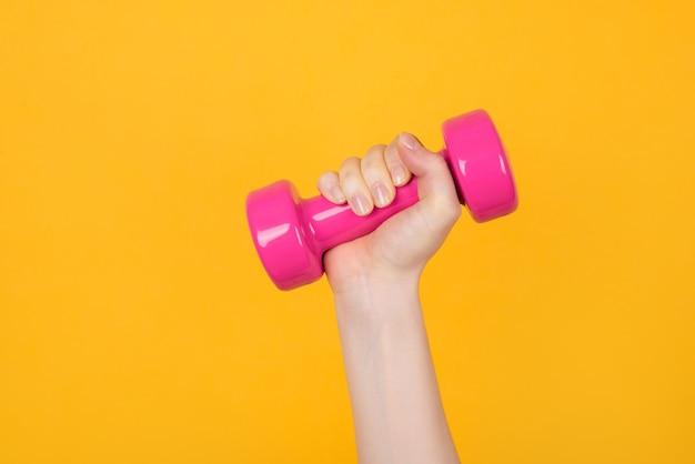 Разработка концепции. обрезанное фото спортивной женщины, держащей в руке розовые гантели, изолированные на желтом фоне